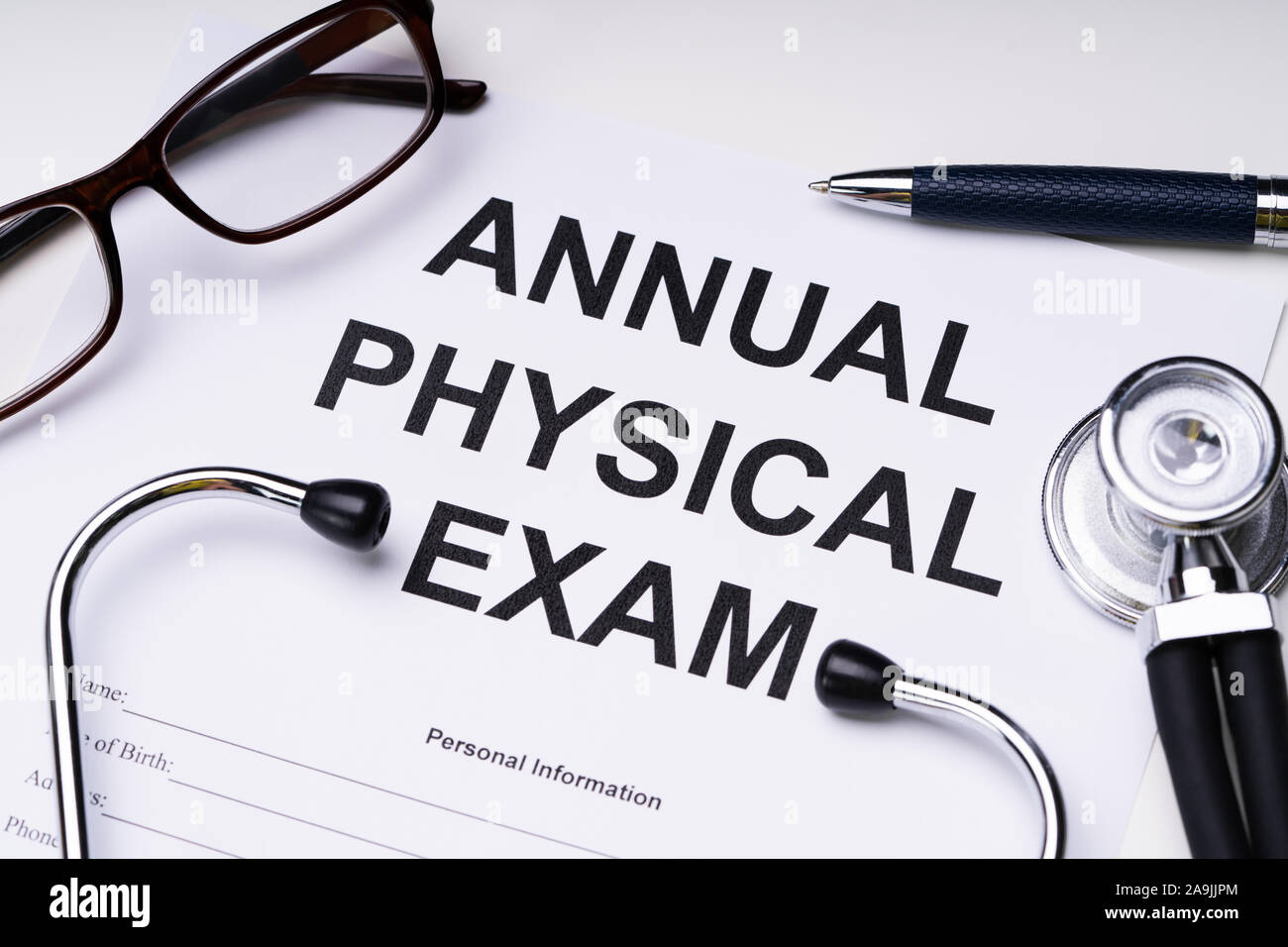 High Angle View Of Annual Physical Exam Form With Stethoscope And Spectacles Over White Desk Stock Photo
