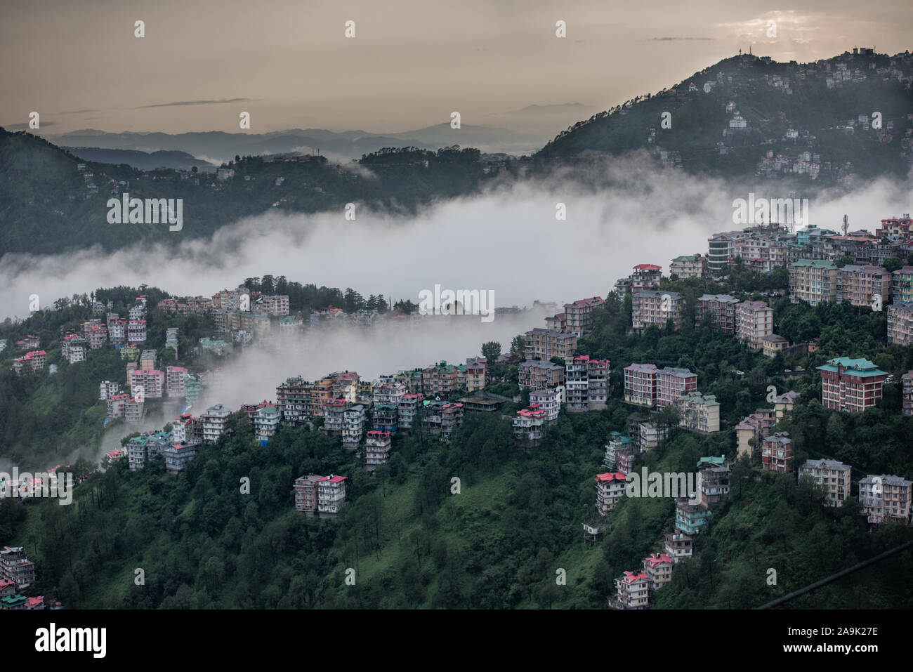 Buildings dotted around the misty mountains during the monsoon season in the Himalayas. Hills around Shimla, Himachal Pradesh, India Stock Photo