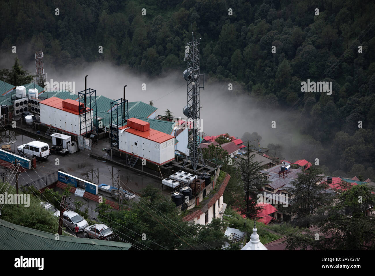 Buildings, mobile masts, telegraph poles on the misty mountains during monsoon season in the Himalayas. Hills around Shimla, Himachal Pradesh, India Stock Photo