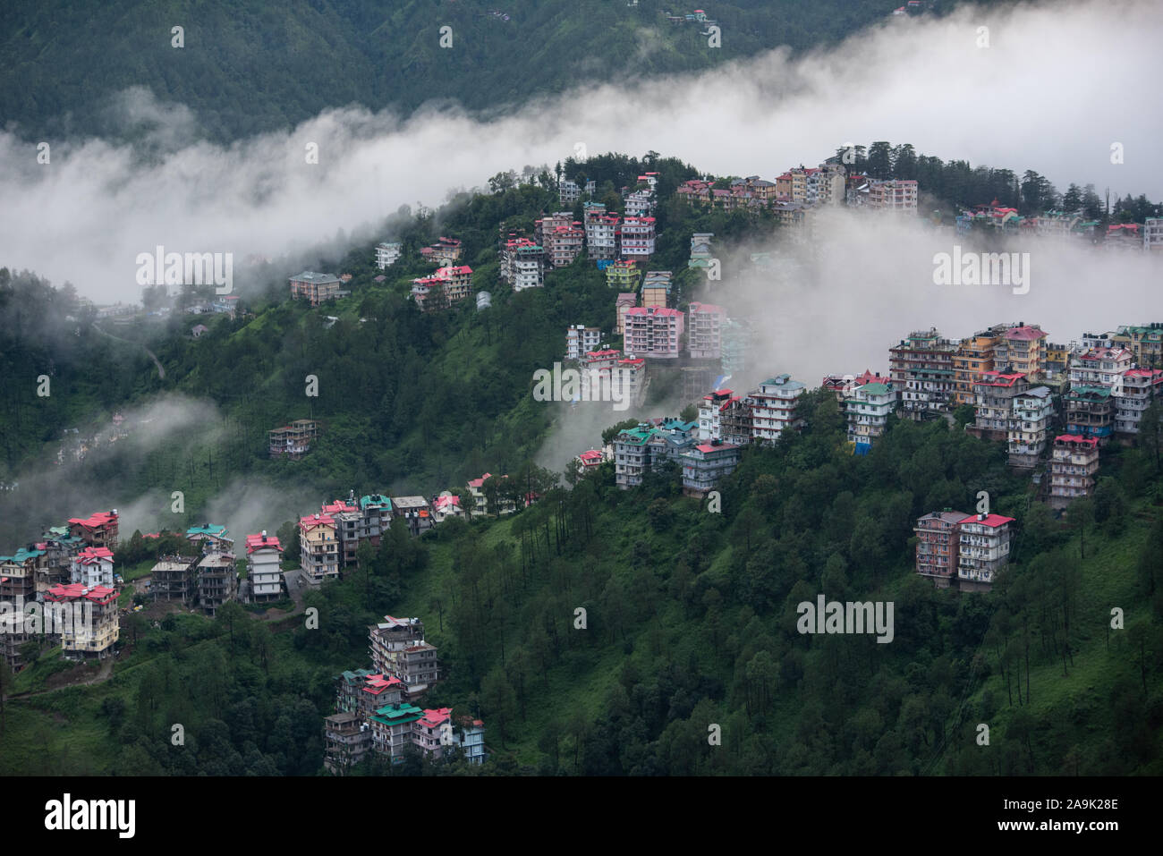Buildings dotted on the misty mountains during the monsoon season in the Himalayas. Hills around Shimla, Himachal Pradesh, India Stock Photo