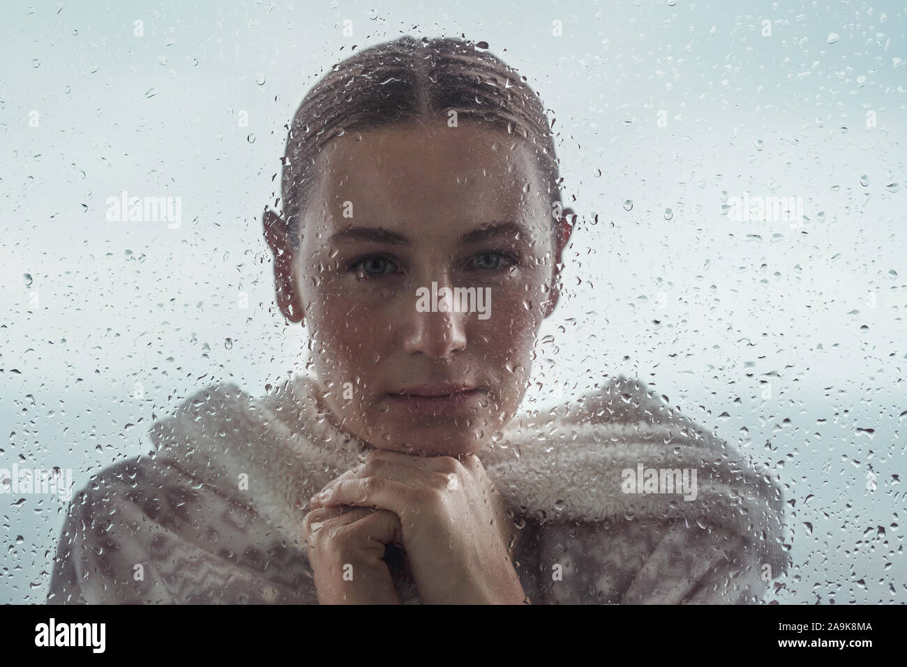 Portrait of a sad woman looking from outdoors into the house through a window covered with raindrops, authentic portrait of a calm girl Stock Photo