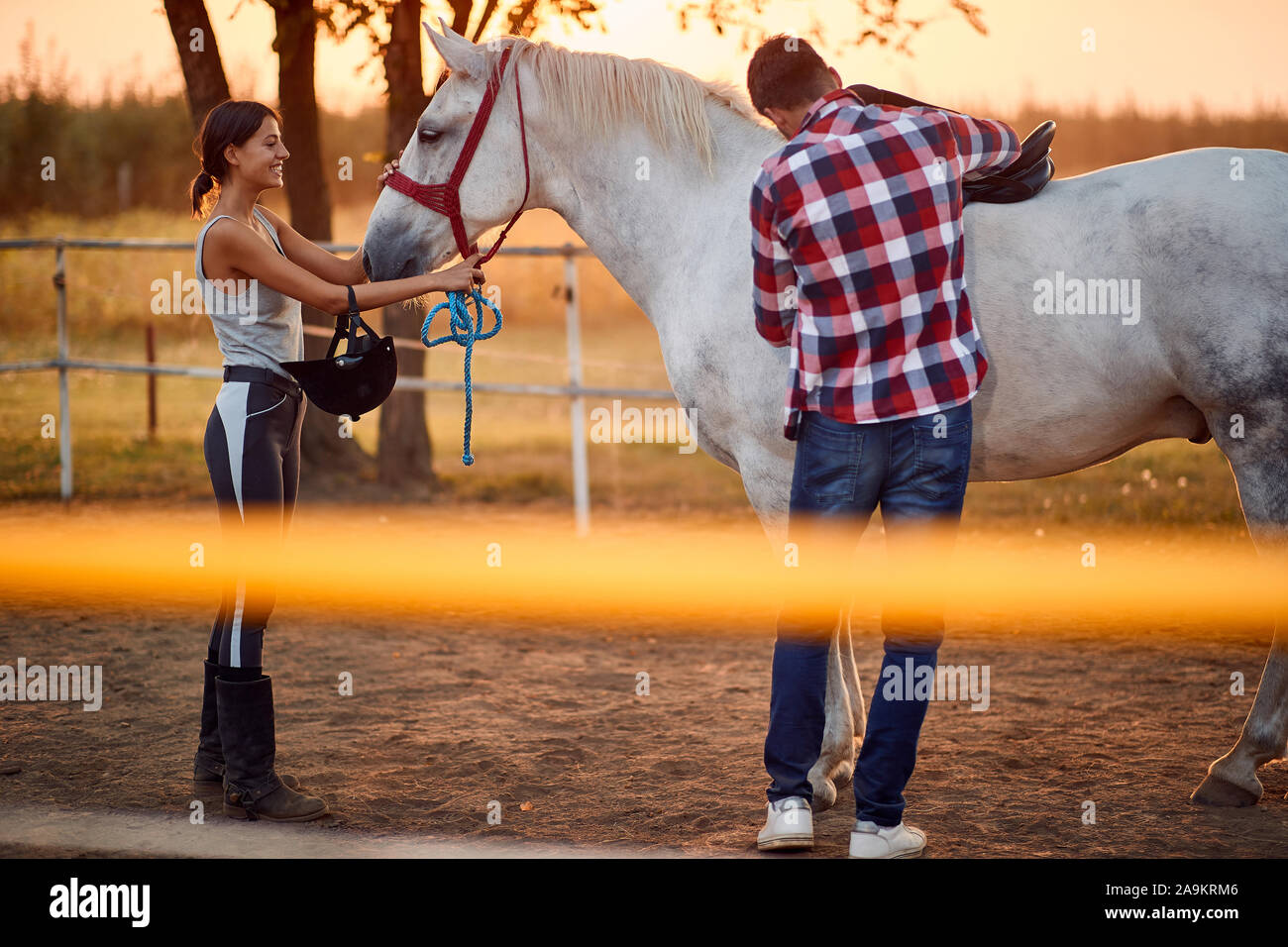 Man And A Woman Tending With Horse Riding Gear Horse Riding Concept Stock Photo Alamy