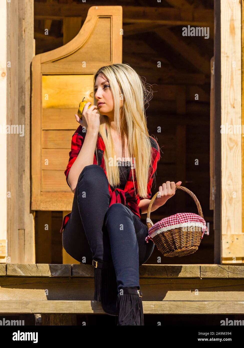 Young woman in village wooden house porch entrance to Western-style bar saloon hand hands hold holding pear fruit and basket Stock Photo