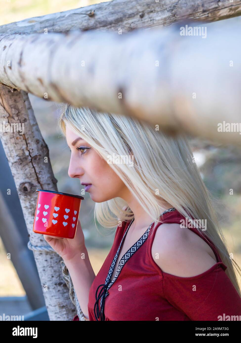 Young woman blonde drinking beverage from Red with hearts mug Stock Photo