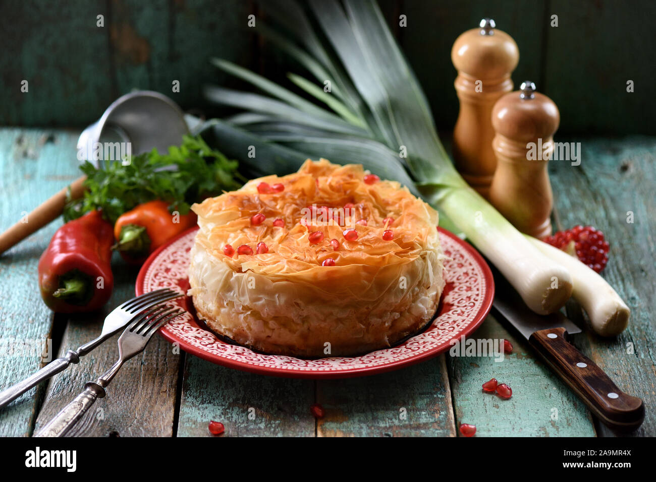 Homemade oriental style phyllo pie with vegetables decorated with pomegranate seeds on old blue boards close up Stock Photo