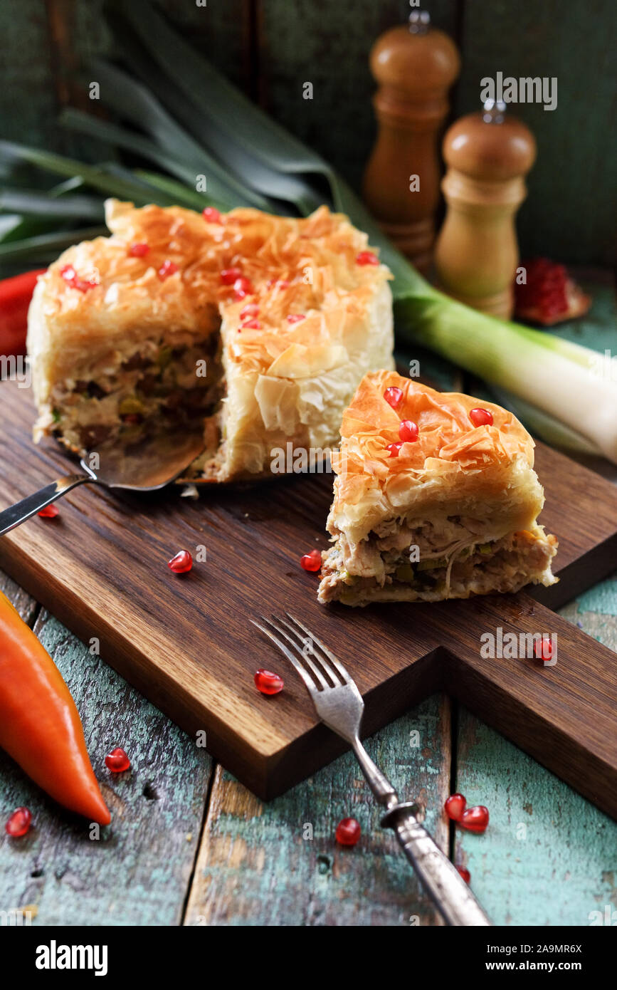 Savory phyllo pastry pie with chicken and vegetables decorated with pomegranate seeds on dark oak board vertical Stock Photo