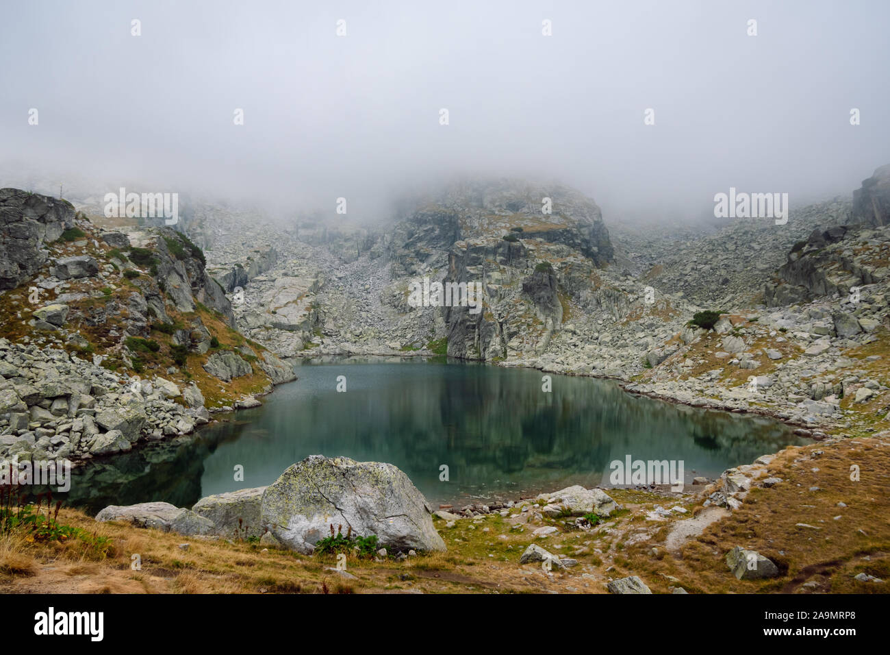 View of a beautiful high mountain lake with calm water surrounded by foggy rocky shore. The Scary Lake, Rila National Park, Bulgaria. Stock Photo