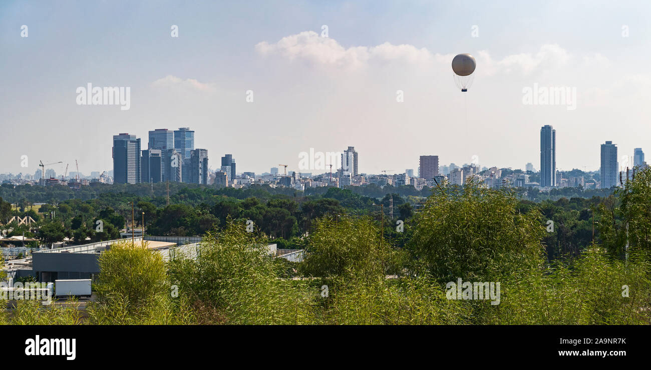 tel aviv city skyline from the university campus with yarkon park and ayalon highway in the middle ground and a hot air balloon in the sky Stock Photo