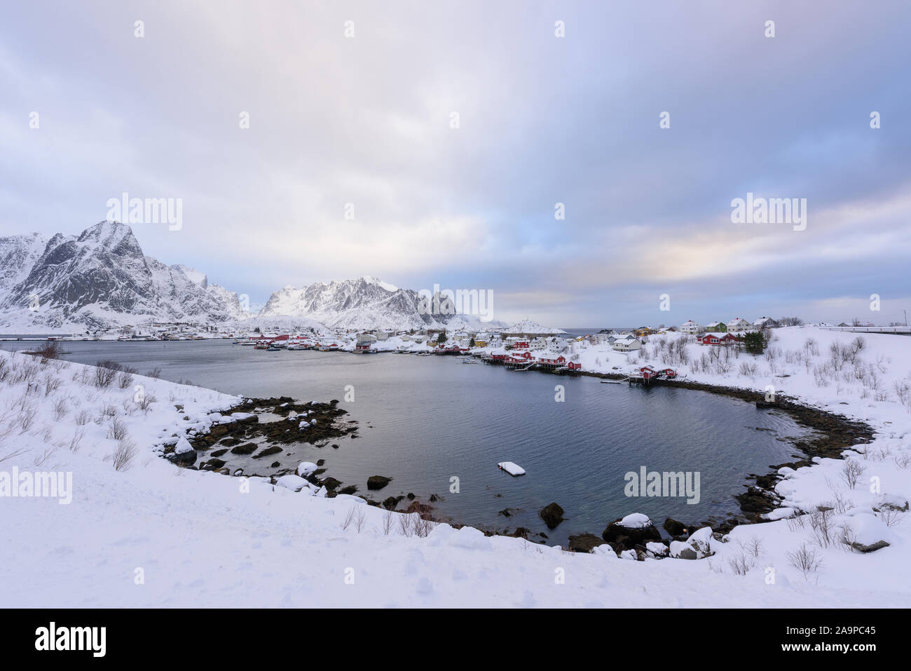 Beautiful village of Reine in Lofoten Islands, Norway. Snow covered winter landscape at sunset. Amazing tourist attraction in the polar circle. Panora Stock Photo