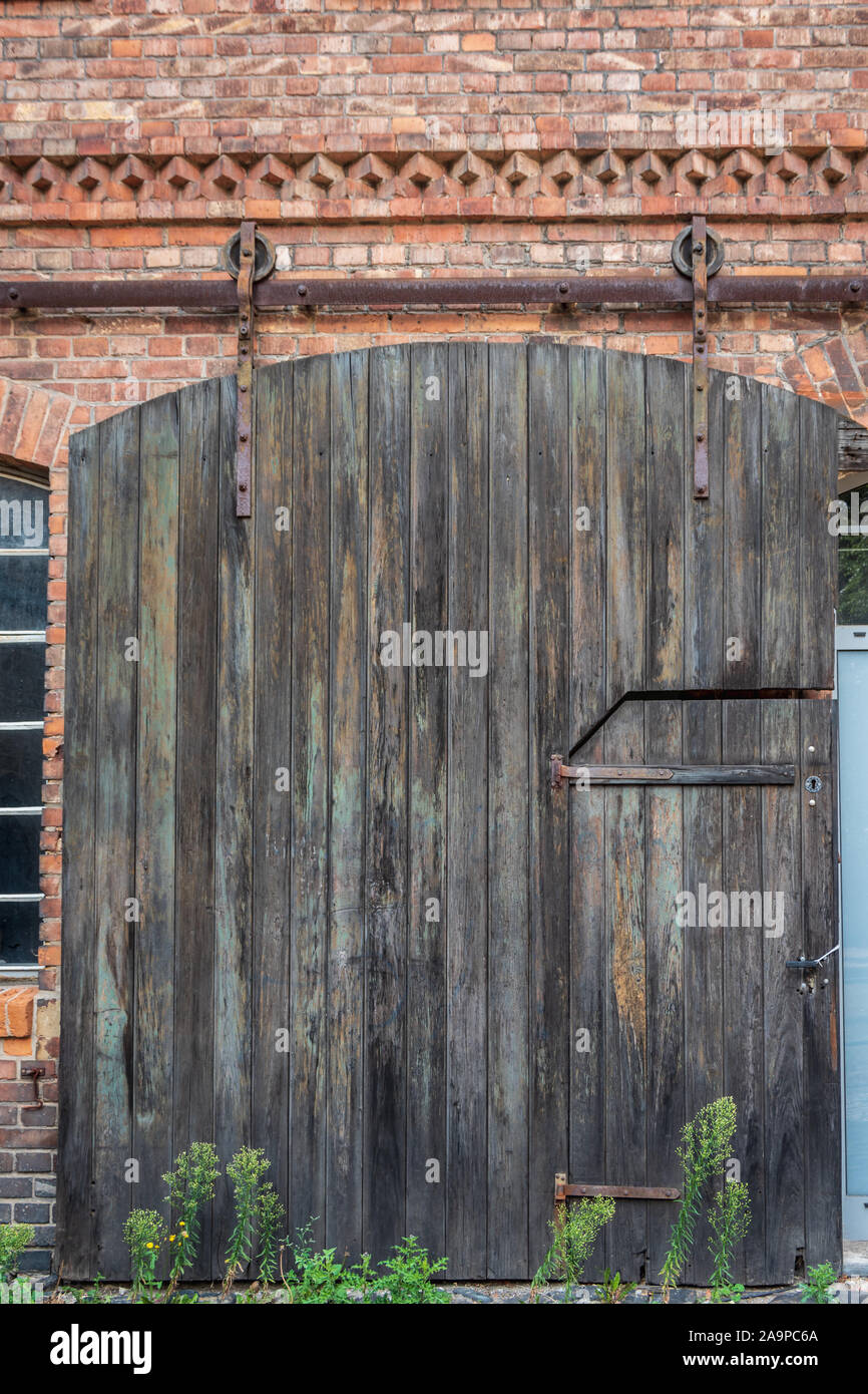 View of a old wooden industrial sliding door on a red brick facade of a building. Vintage Strap Door. Industrial wheel steel barn wood door. Stock Photo