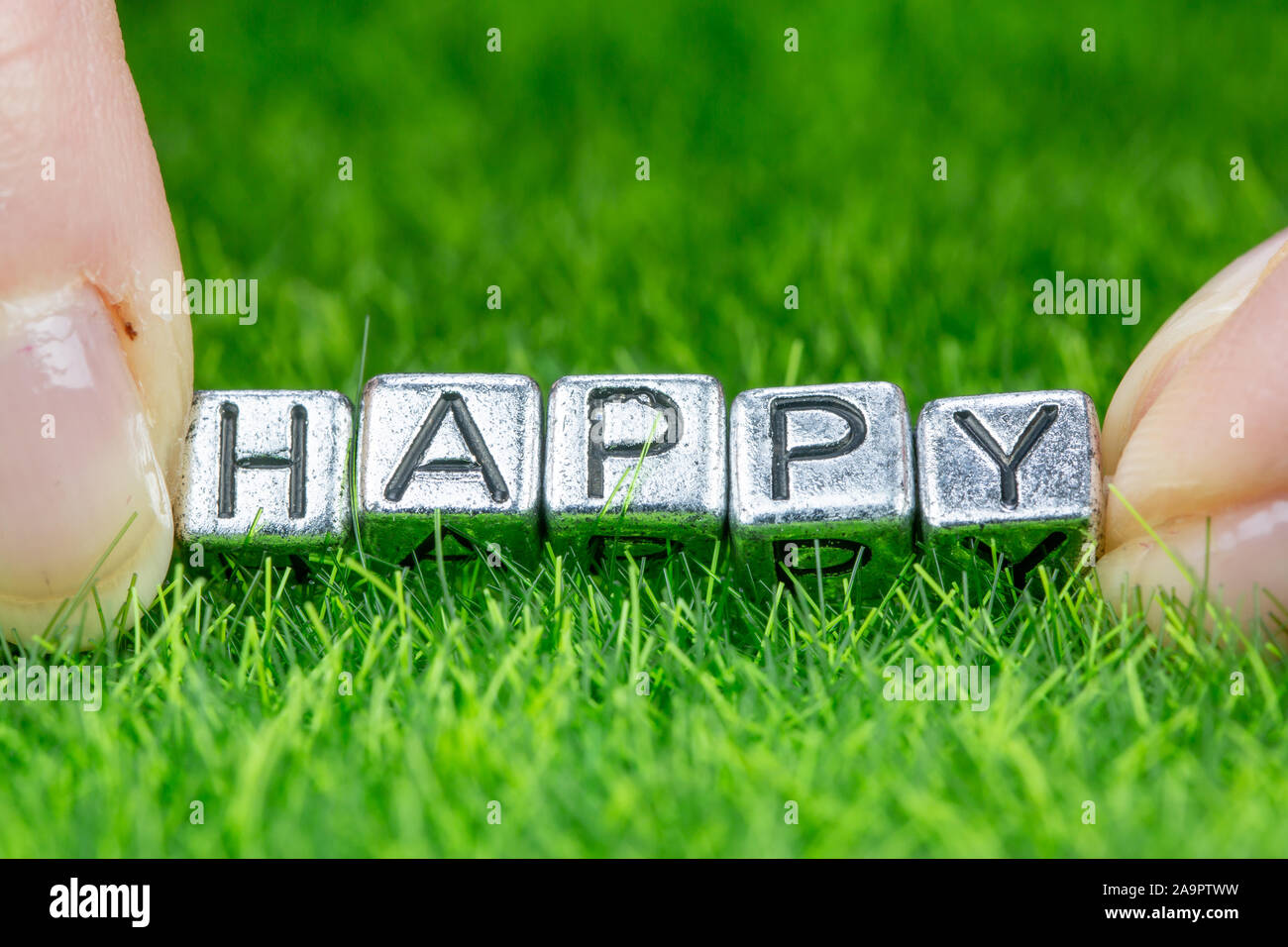 Close up on word HAPPY written in metal letters laid on grass and held between the fingers of a woman. Concept of wellness background Stock Photo