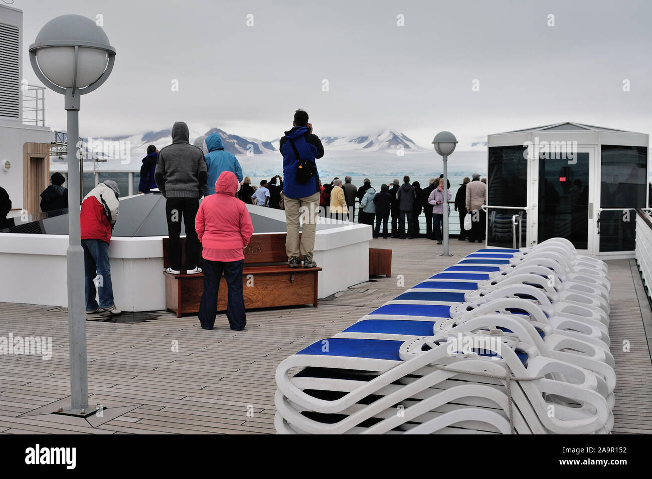 Passengers on the deck of a cruise ship sailing past the Lilliehookbreen glacier on the west coast of Spitsbergen (latitude 79.20N). Stock Photo