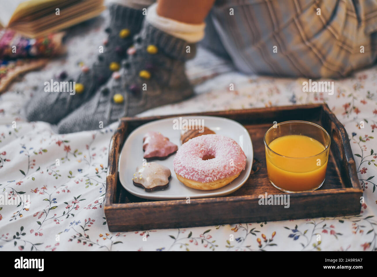 Young woman lying on colorful bed having breakfast on holidays. Morning in a cozy warm bedroom with natural juice Christmas cookies and and donut. Hap Stock Photo