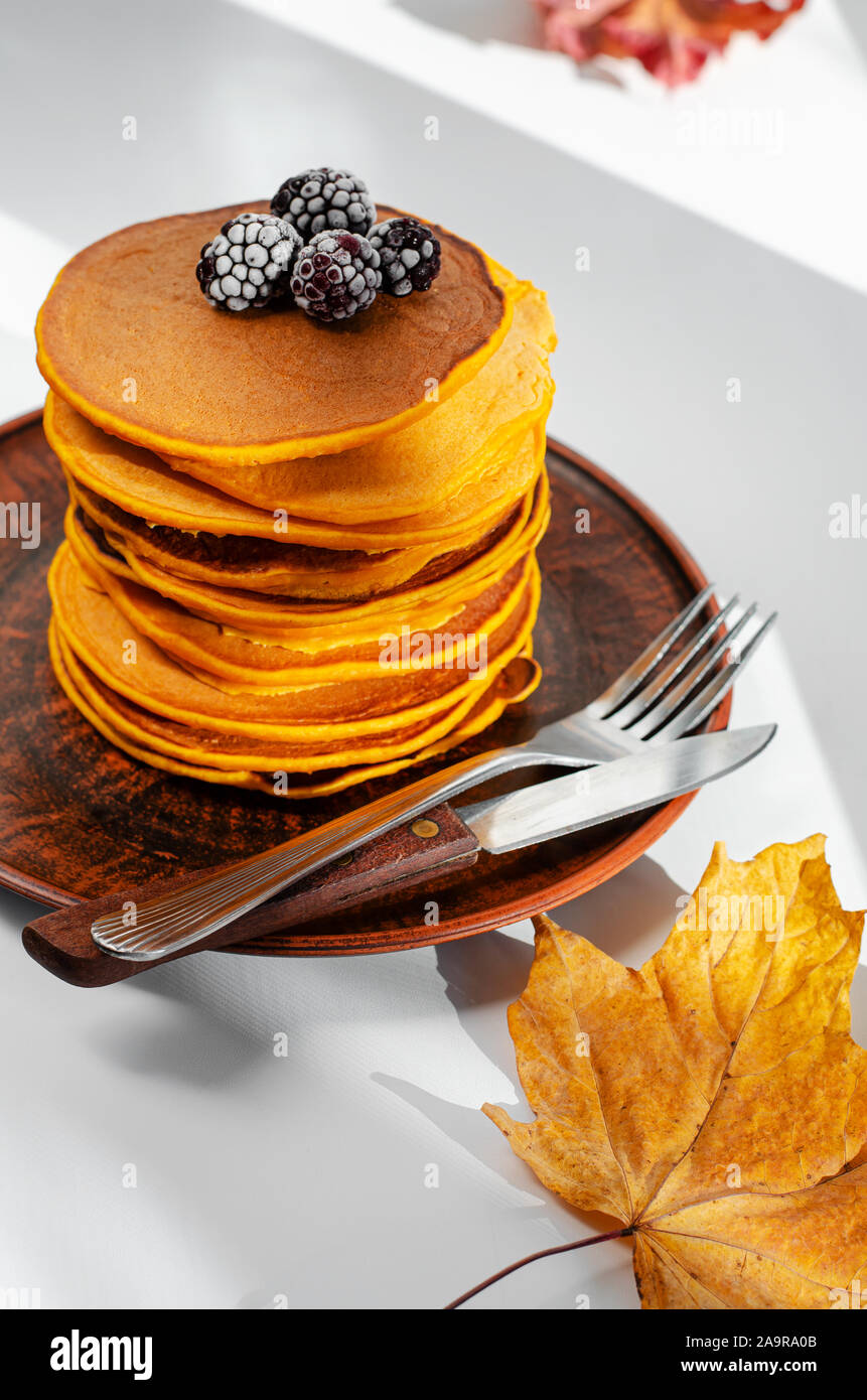 A heap of pumpkin pancakes with blackberries. Delicious breakfast. Vertical Stock Photo