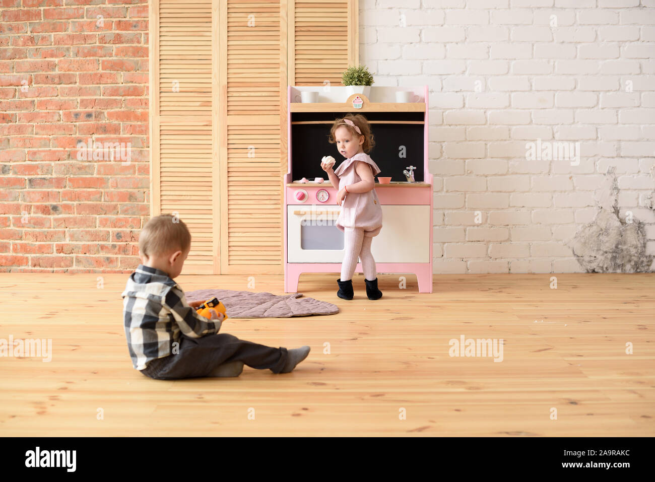 Family and children concept. Toddler boy playing on floor and cute little girl eating sweets at play kitchen in big empty room copy space Stock Photo