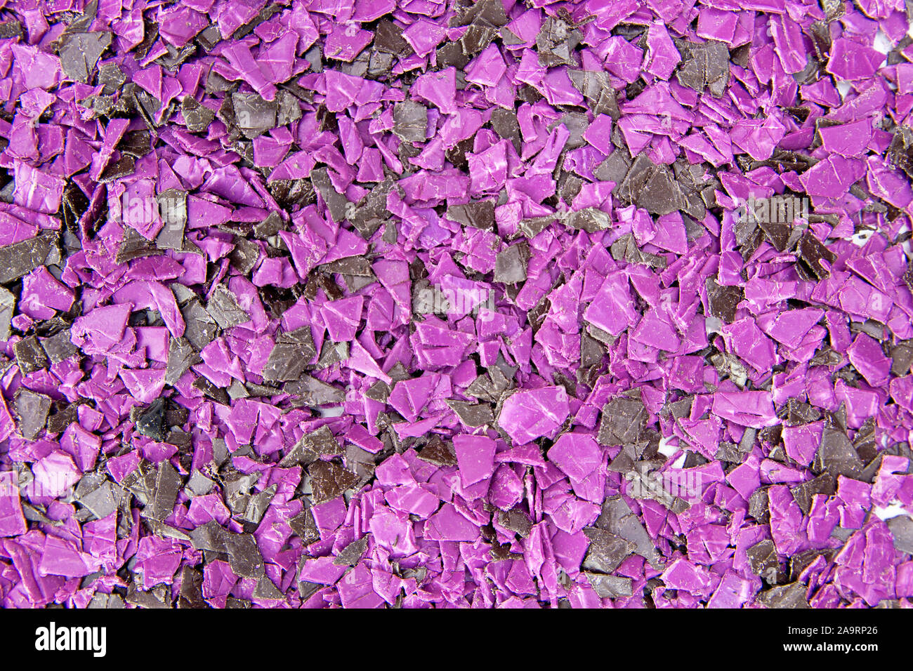 pieces of plastic for recycling. Crushed polyethylene, polypropylene close-up. The view from the top Stock Photo