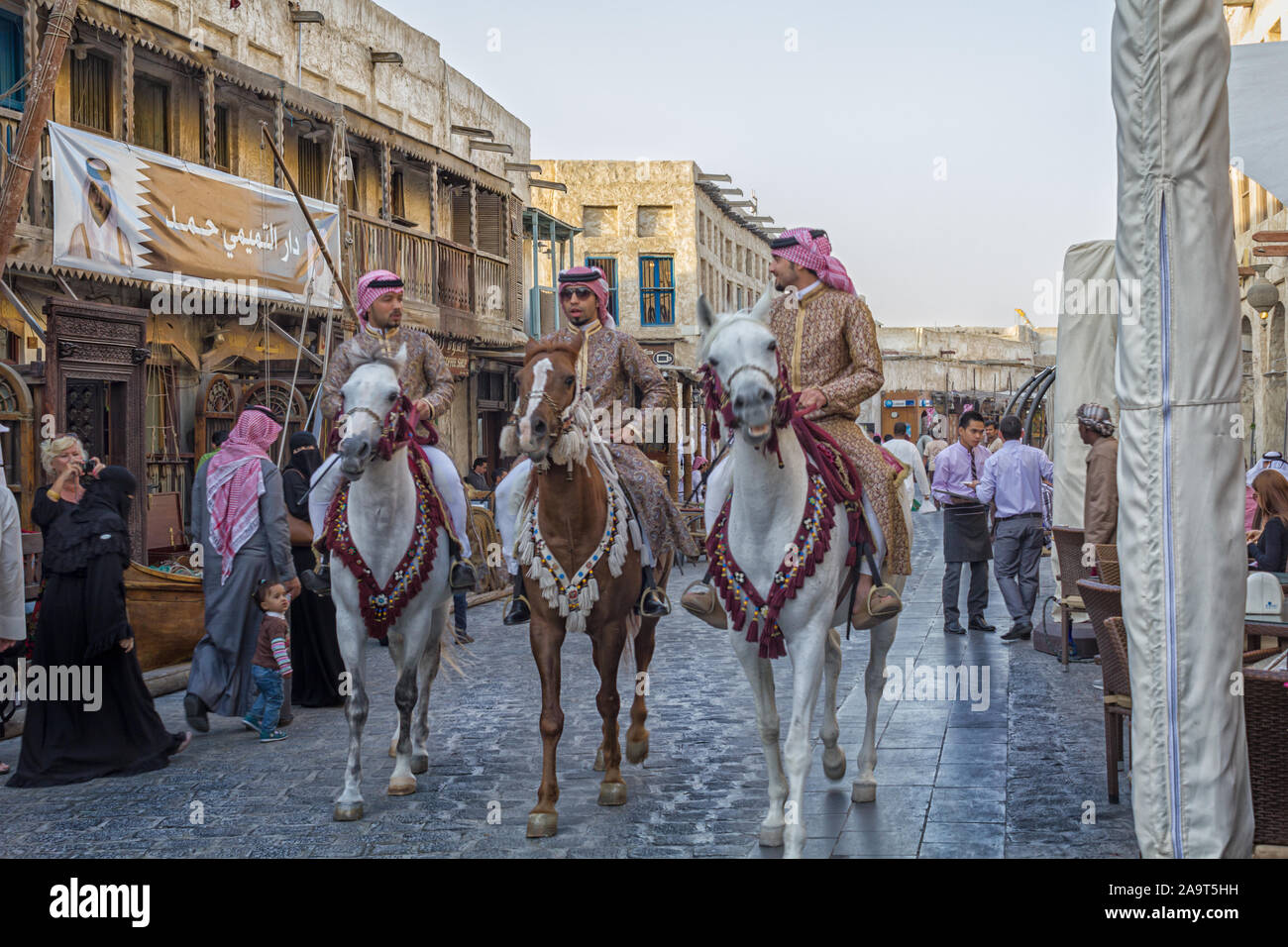 Doha-Qatar, January 24,2013: Souk Waqif in Doha Qatar main street day light view with traditional guards riding horses and people Stock Photo