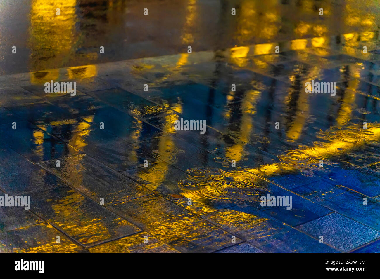 Blurred reflection of a bright building in a puddle on the asphalt. Rain in the city at night. Abstract vivid colorful background. Selective focus Stock Photo