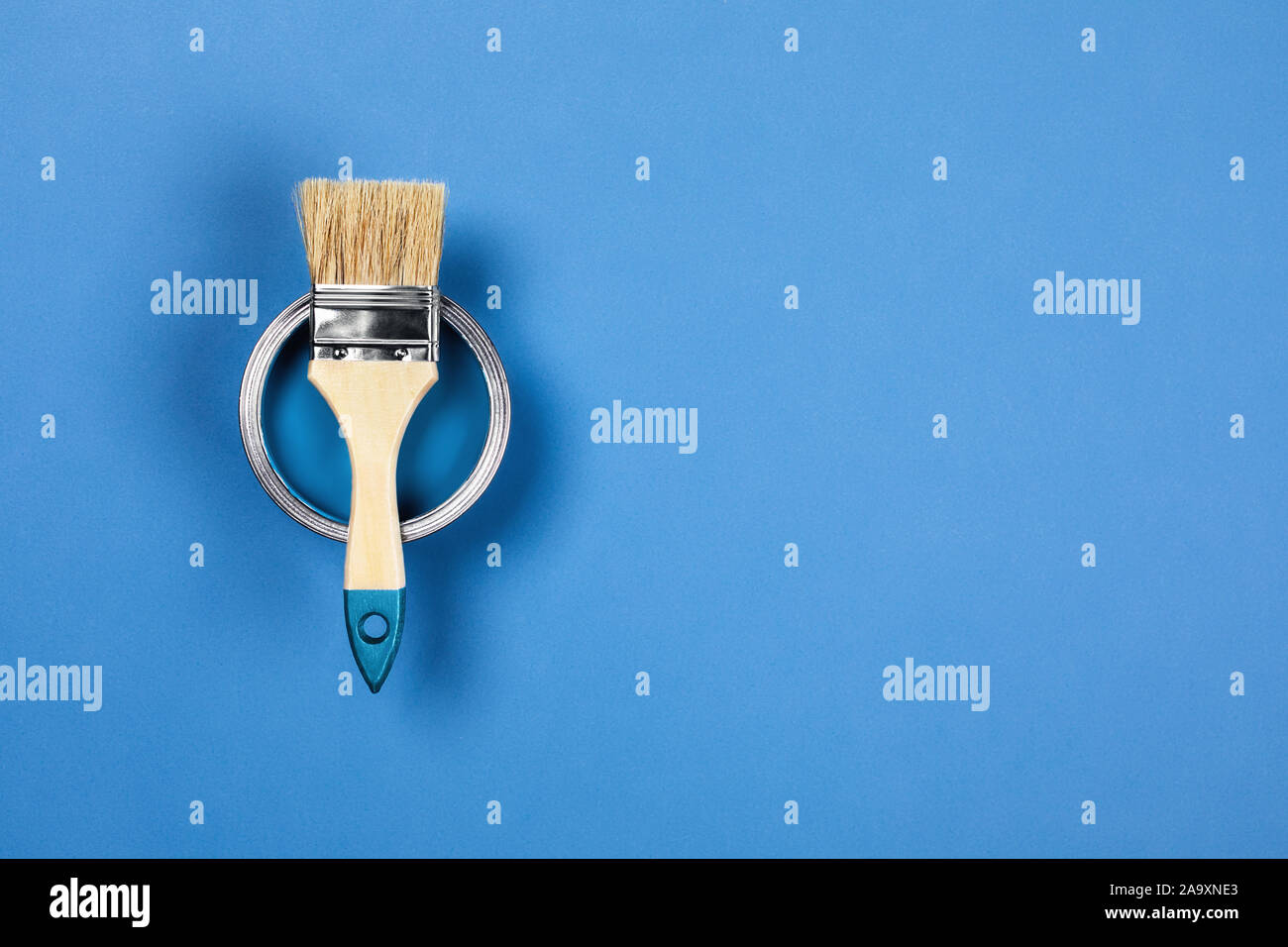 Renovation concept. Blue background with color paint jar and one brush. Flat lay, top view, copy space. Stock Photo
