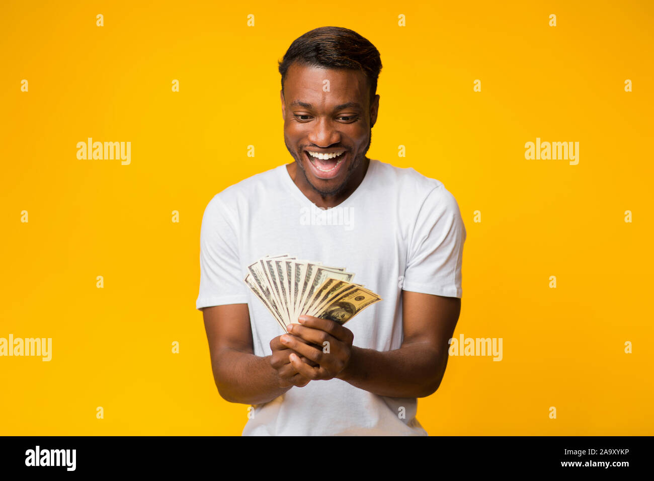 Happy Afro Man Holding Money Standing Over Yellow Studio Background Stock Photo