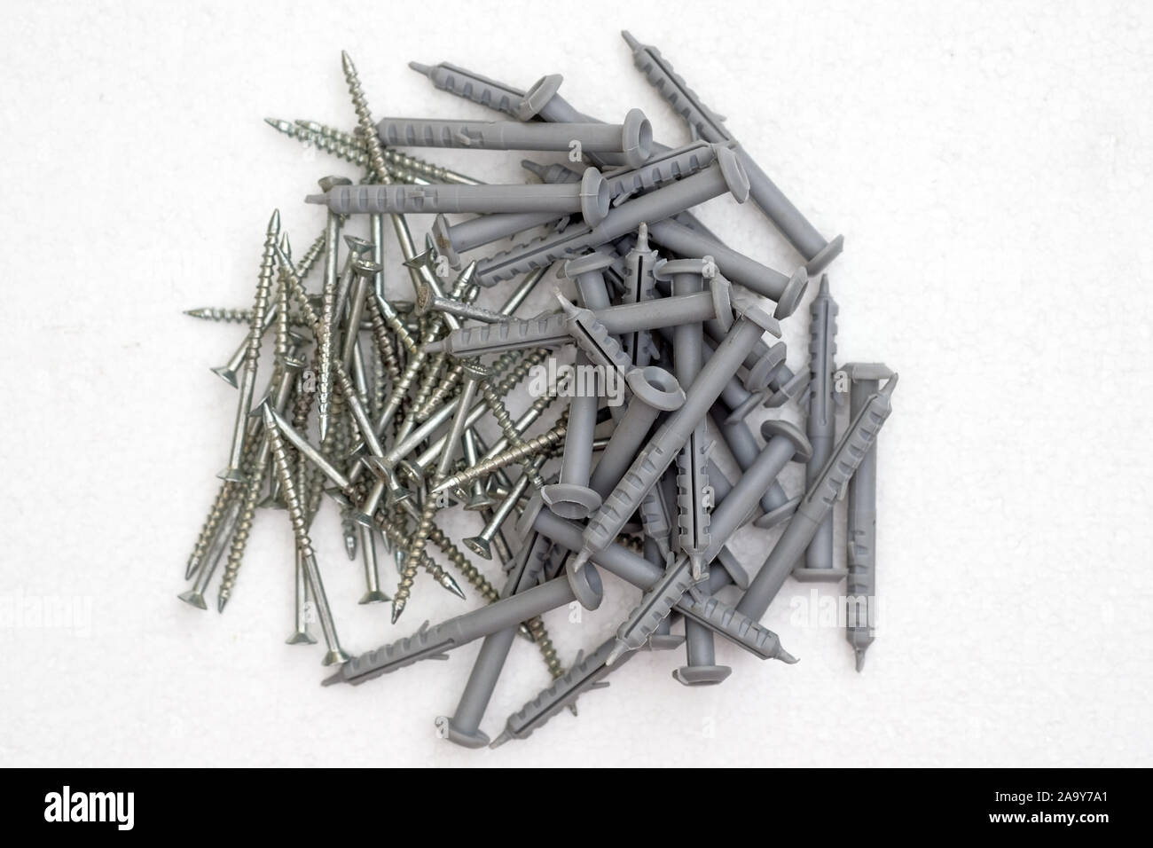 Gray plastic dowels with metal screws on a white background top view. Construction material. An anchor is a fastener to hold any structure. Stock Photo