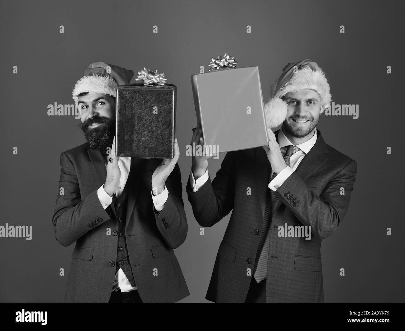 Businessmen With Cheerful Faces Hold Red And Blue Present Boxes Men In Smart Suits And Santa Hats On Blue Background Business And Celebration Concept Managers With Beards And Christmas Gifts Stock Photo