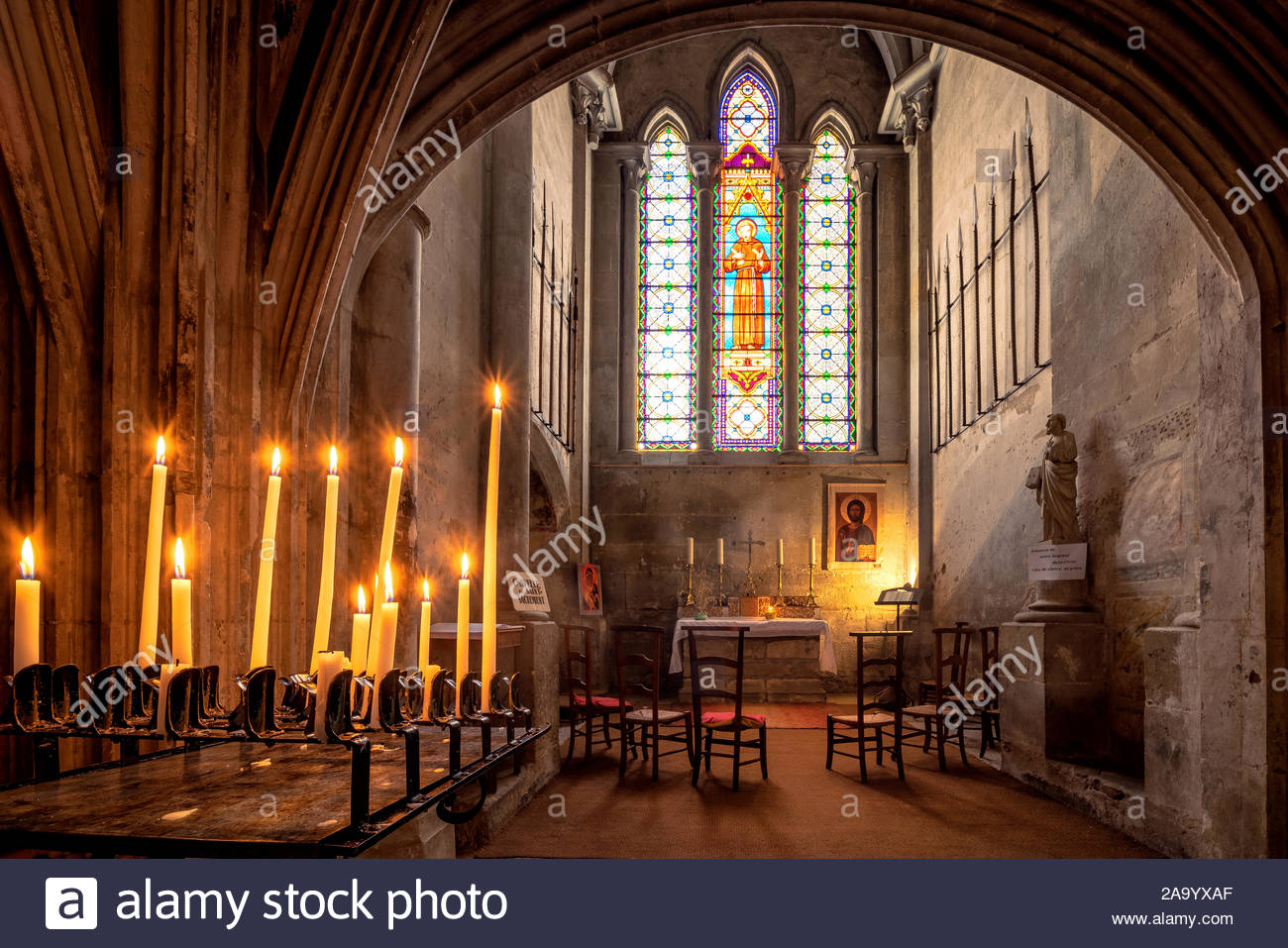 Saint-Antoine-l'Abbaye abbey church : candles in front of the Blessed Sacrament chapel Stock Photo