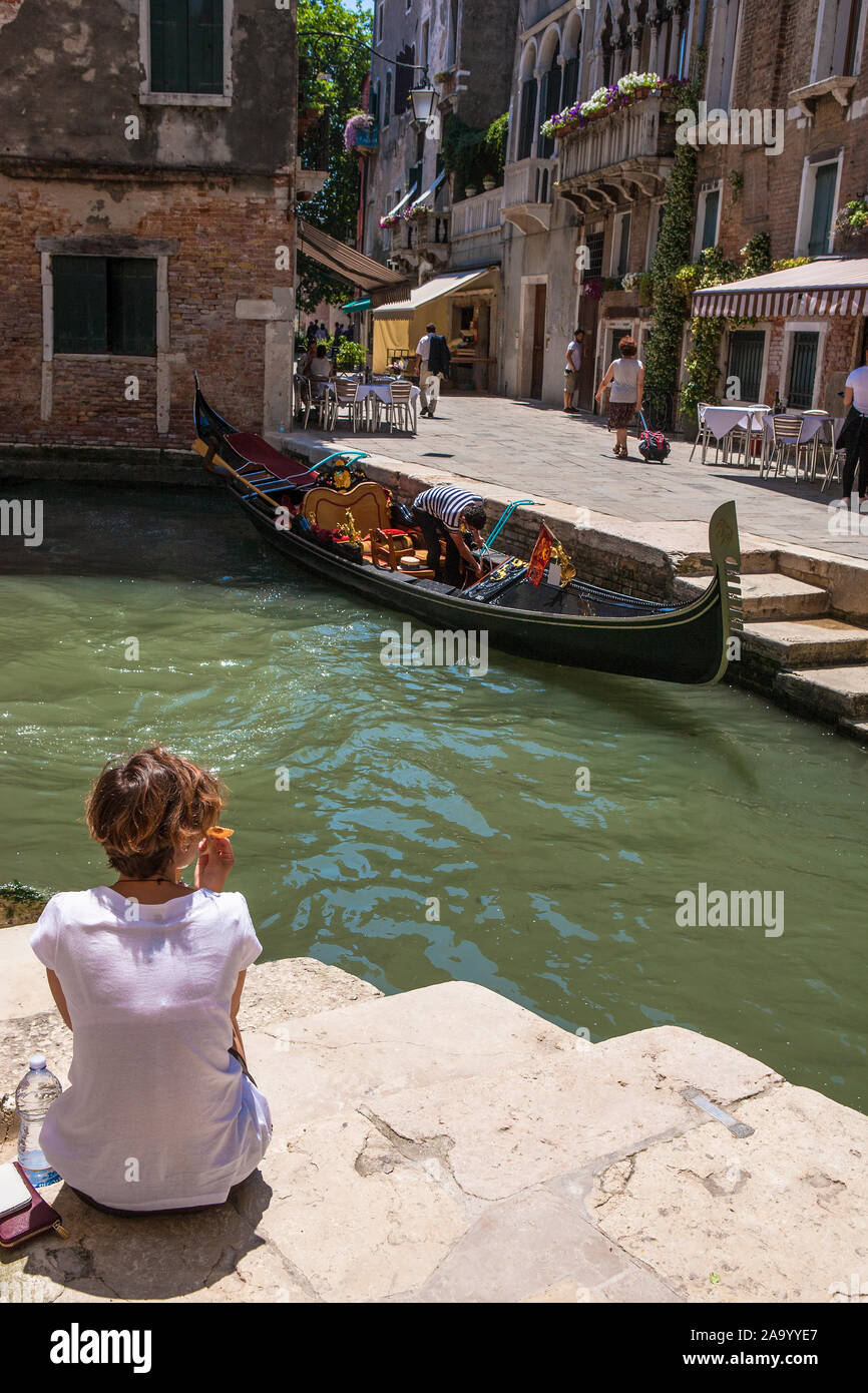 A girl sits on the steps by a Venetian canal with a gondola opposite: Rio del Megio and Calle Larga, Santa Croce, Venice, Italy Stock Photo