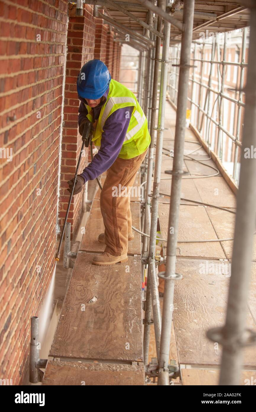 A person wearing safety gear and standing on a scaffold, uses a spray gun while working on the exterior of Gilman Hall, on a cold day at the Johns Hopkins University, Baltimore, Maryland, March 11, 2009. From the Homewood Photography Collection. () Stock Photo