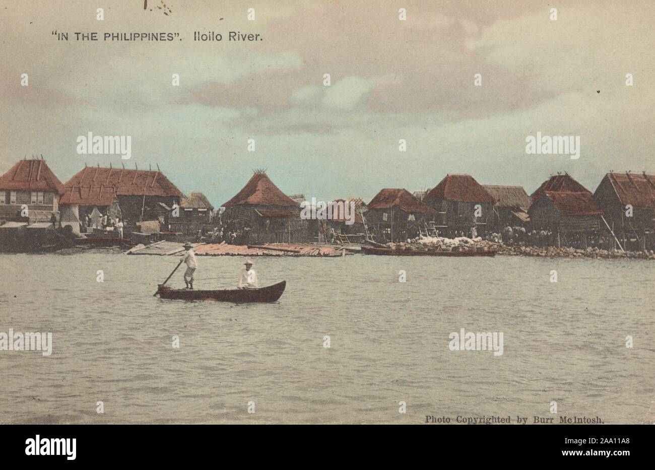 Illustrated postcard of a boat with two fishermen floating along Iloilo River, with thatched roof houses along the river bank, Panay Island, the Philippines, by photographer Burr McIntosh, published by H. Hagemeister Co, 1905. From the New York Public Library. () Stock Photo