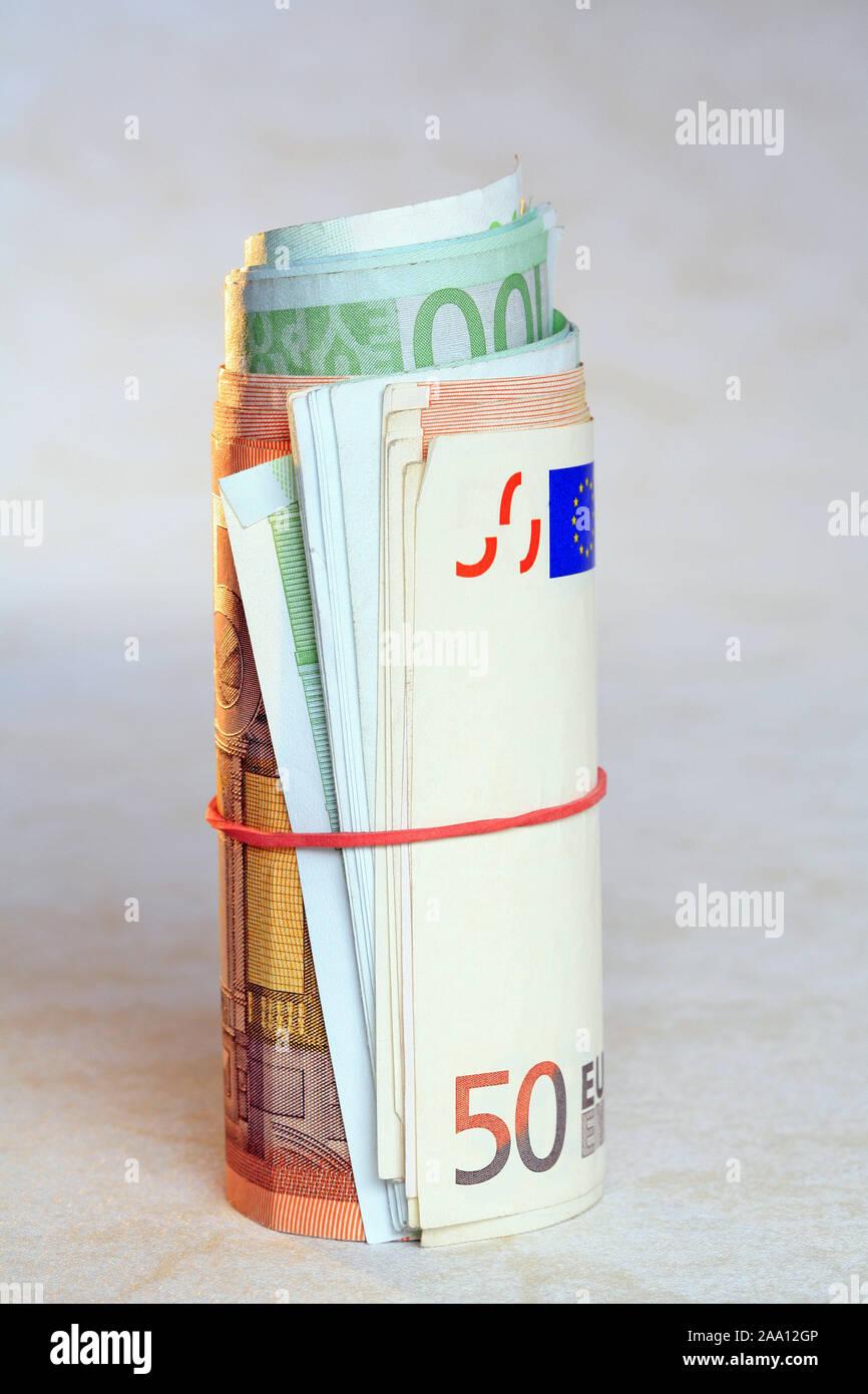Zusammengerollte Euro Geldscheine mit einem Gummiring / Rolled Euro bank notes with a rubber ring Stock Photo
