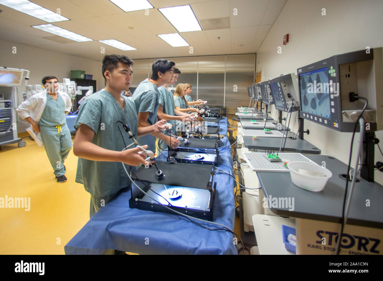 Watching their progress on monitors at a summer surgery workshop, teenagers in medical scrubs practice remote control laproscopic surgery techniques under a doctor's watchful eye at an Orange, CA, hospital. Stock Photo