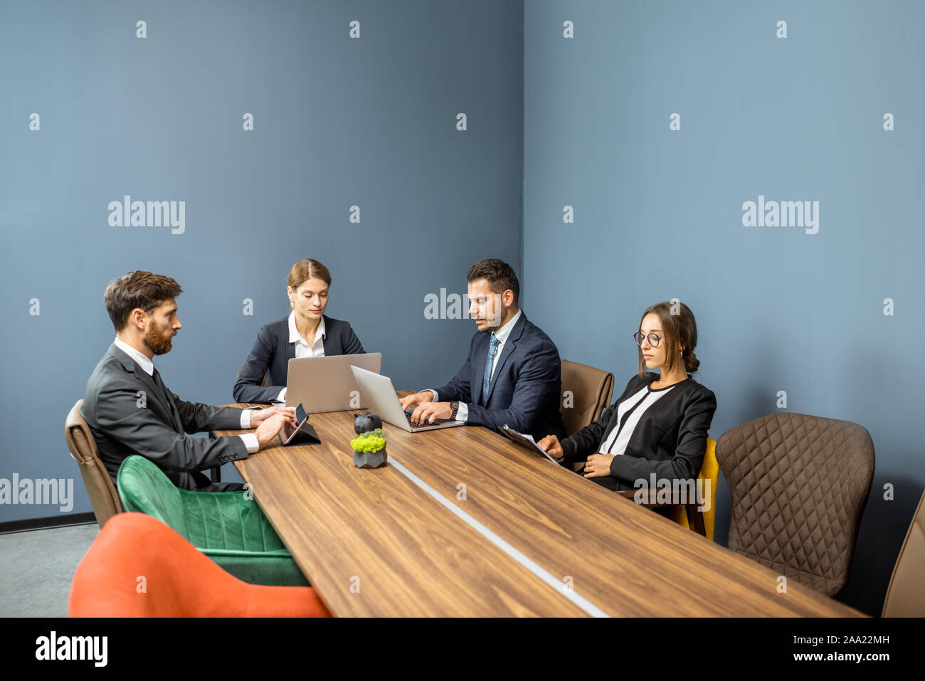 Group of business people strictly dressed in the suits sitting at the big table during a conference in the meeting room Stock Photo