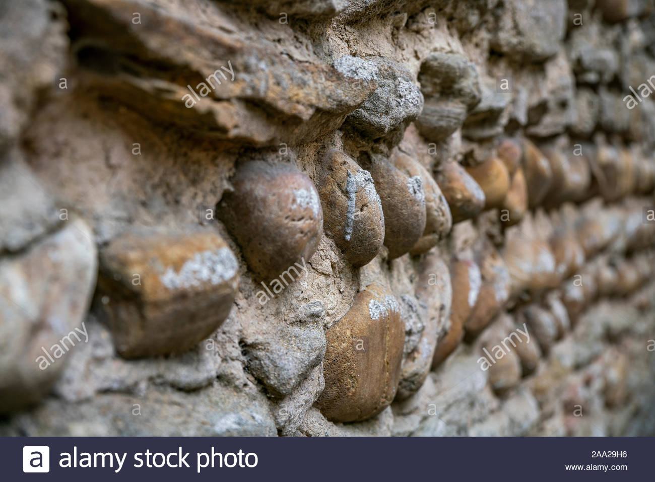 Medieval pebble stone wall in Saint-Atoine-l'Abbaye (France) Stock Photo