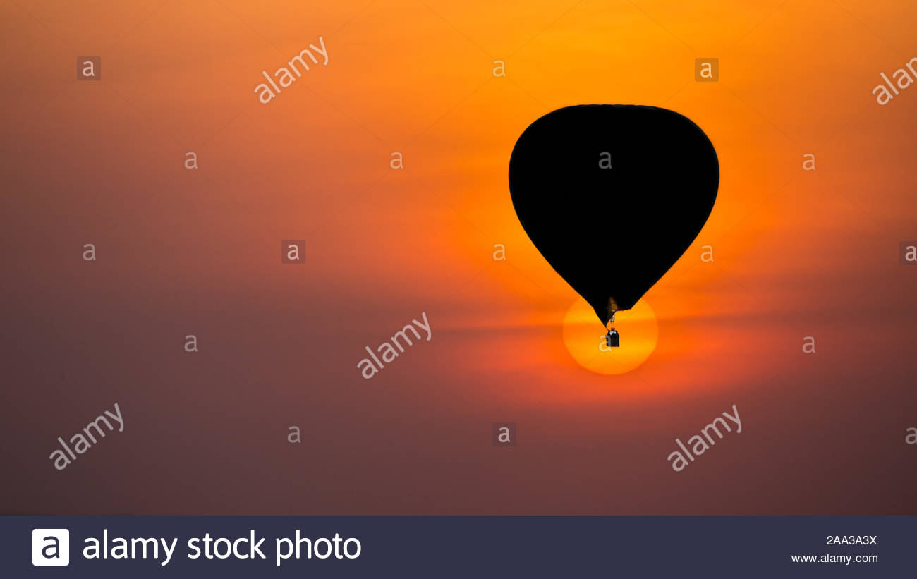 Silhouette of a hot sir nalloon on safari against a perfect round rising orange sun background Stock Photo