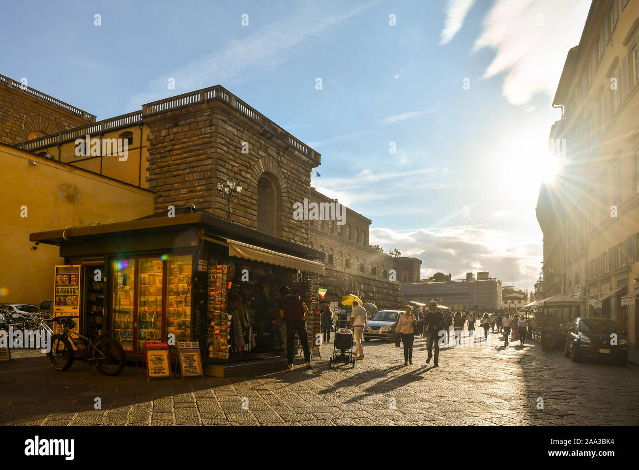 Backlight view of the historic centre of Florence, Unesco World Heritage Site, with a newsstand in front of Palazzo Pitti museum, Tuscany, Italy Stock Photo