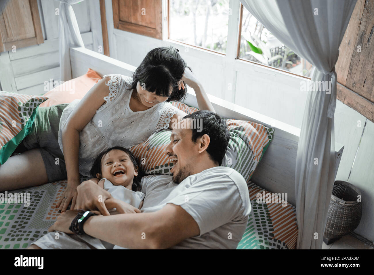 Happy family playing together on the bed Stock Photo