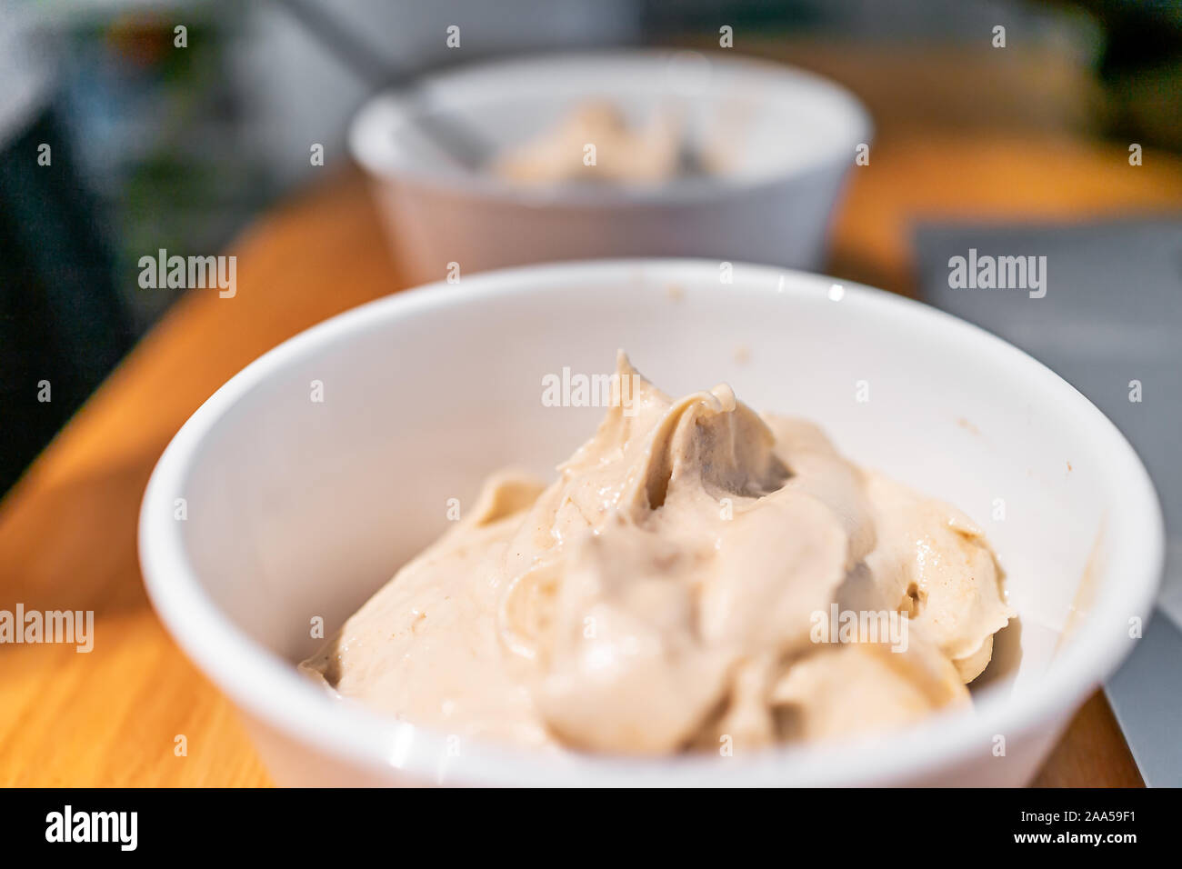 soft serve vanilla ice cream bowls with bokeh background of table and laptop puter made with banana nice cream vegan dessert 2AA59F1