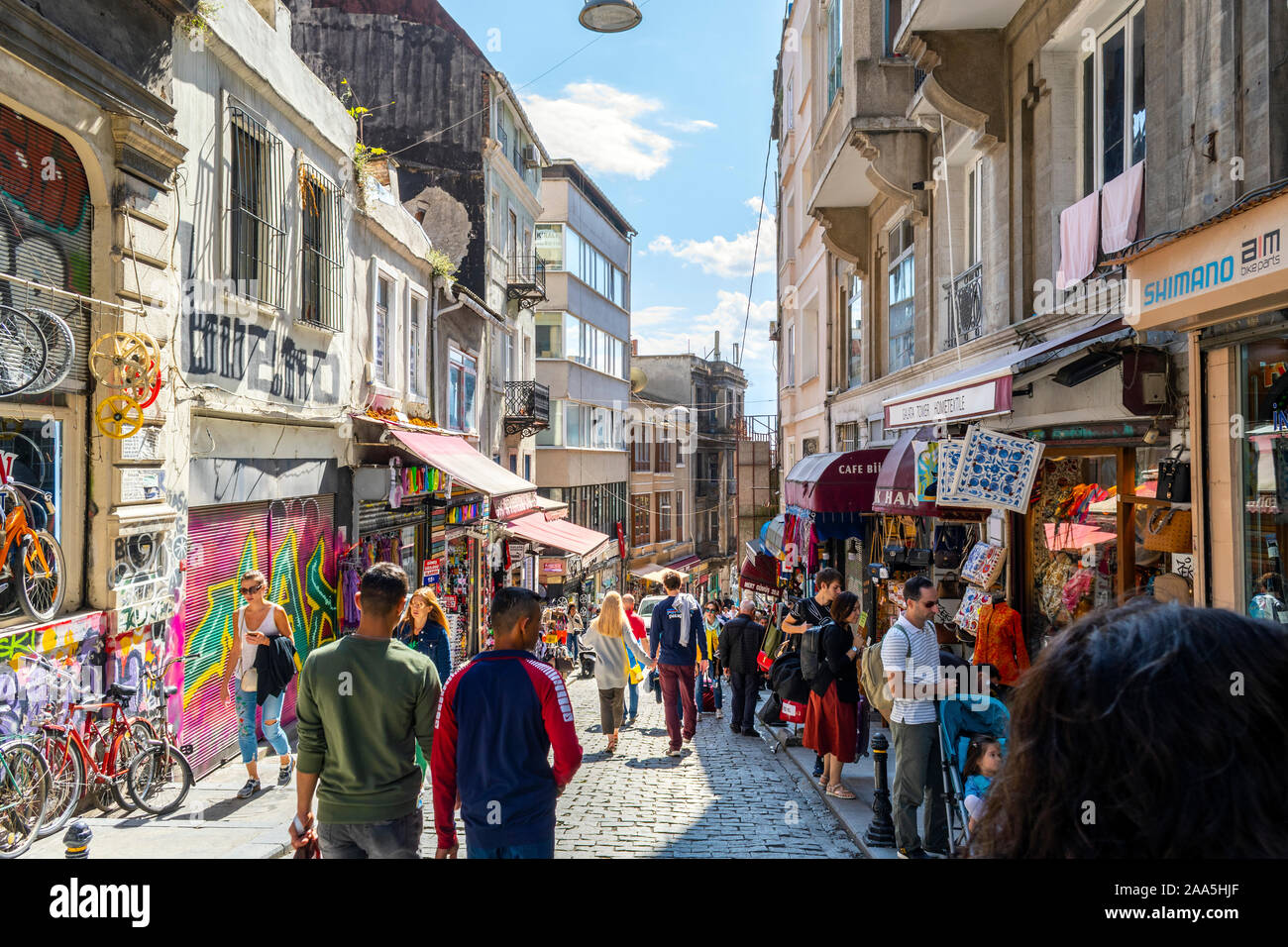 Tourists walk downhill past shops and cafes on a busy summer day in the Galata Karakoy district of Istanbul, Turkey Stock Photo