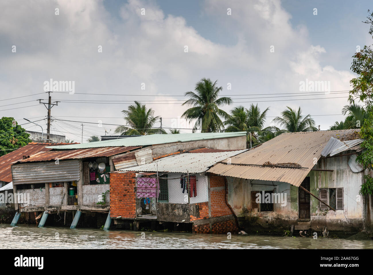 Cai Be, Mekong Delta, Vietnam - March 13, 2019: Along Kinh 28 canal. Row of slum-like poor houses built on stilts and on shore with corrugated roof pl Stock Photo