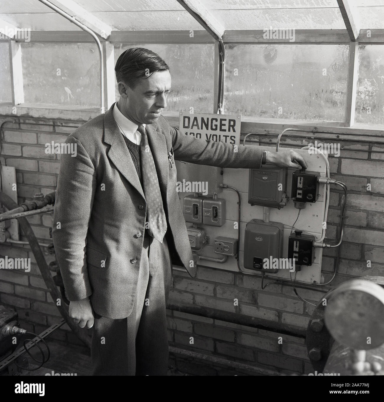 1950s, historcial, agricutulture, a man in a suit with his tie outside a sweater standing by the meters in a large greenhouse, England, UK. Stock Photo