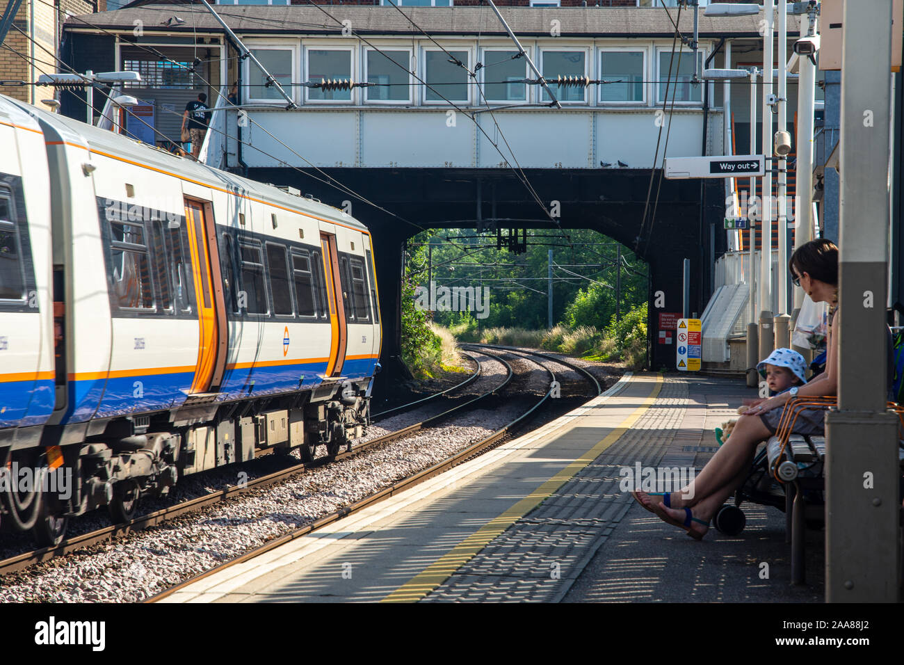 London, England, UK - July 24, 2019: Passengers wait for a train at Kensal Rise Station on a sunny summer day on the London Overground. Stock Photo