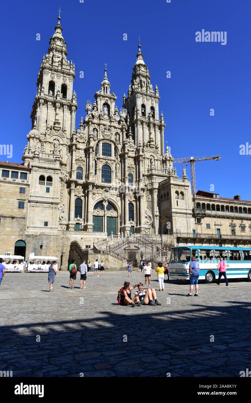 Cathedral with pilgrims taking pictures at Plaza del Obradoiro with old bus from exhibition. Santiago de Compostela, Spain. July 28, 2019. Stock Photo