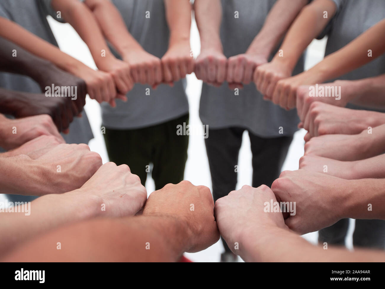 group of young people making a circle out of their hands Stock Photo