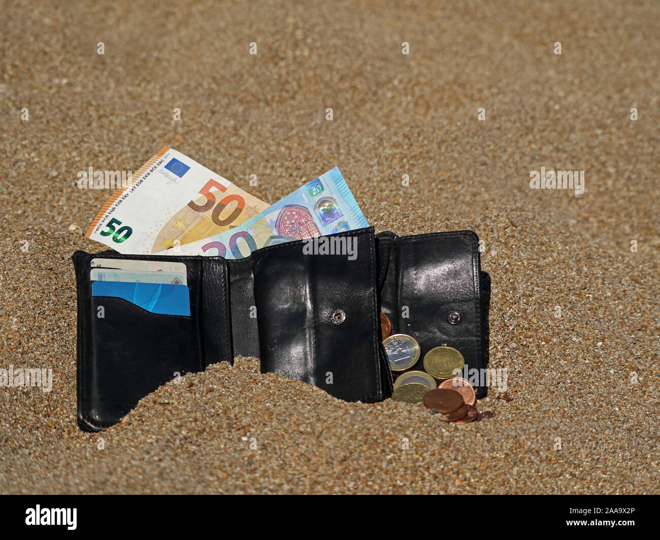 open black wallet with euro banknotes and coins in the sand on beach Stock Photo