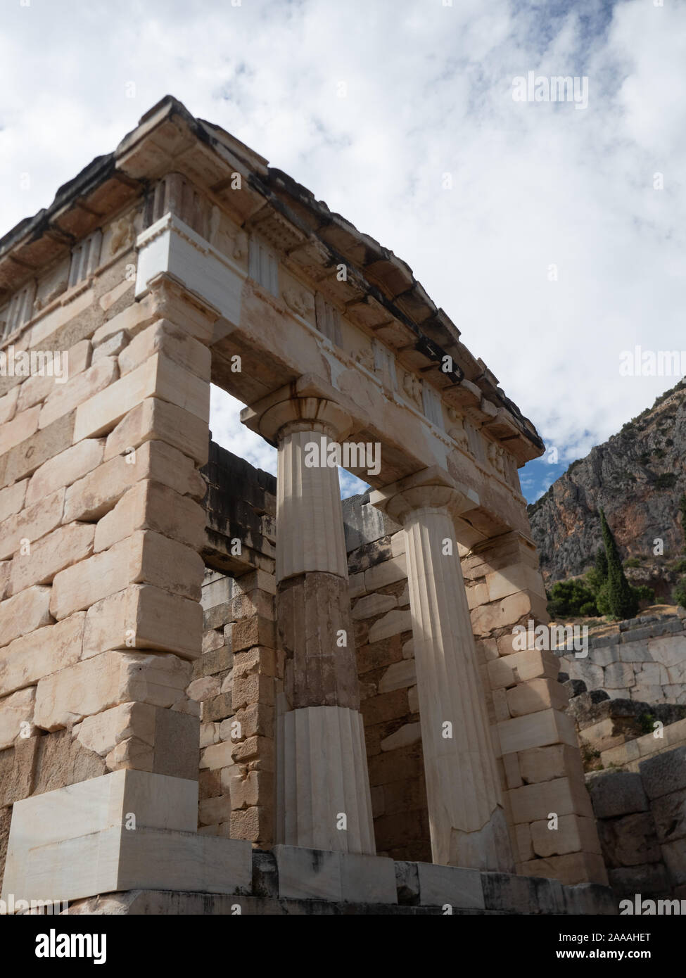The rebuilt Athenian Treasury with doric columns and stone block construction at Delphi in Greece. Stock Photo