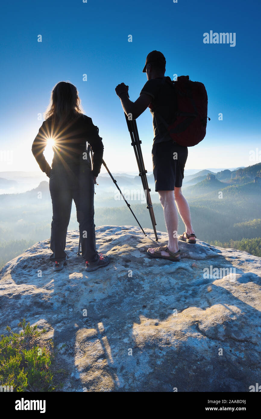 Silhouettes of photographers standing on peak. Photographers work on the top of mountain with amazing view into wakeuping landscape. Stock Photo