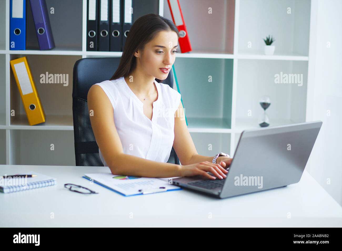 Woman sitting at desk, working on laptop in modern office Stock Photo