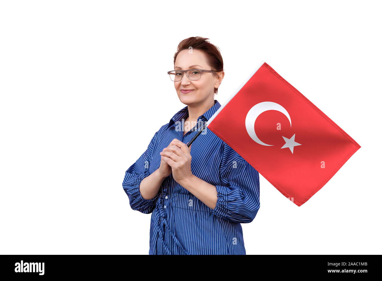 Turkey flag. Woman holding Turkish flag. Nice portrait of middle aged lady 40 50 years old holding a large flag isolated on white background. Stock Photo