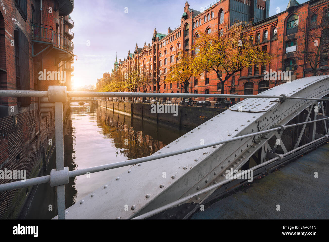 Arch bridge over canals in the Speicherstadt of Hamburg, Germany, Europe. Historical red brick building lit by warm soft golden sunset light. Stock Photo